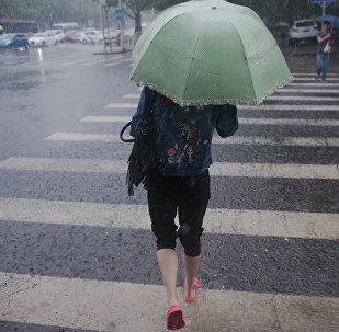 Девушка с зонтом переходит улиц во время сильного дождя. Архивное фото