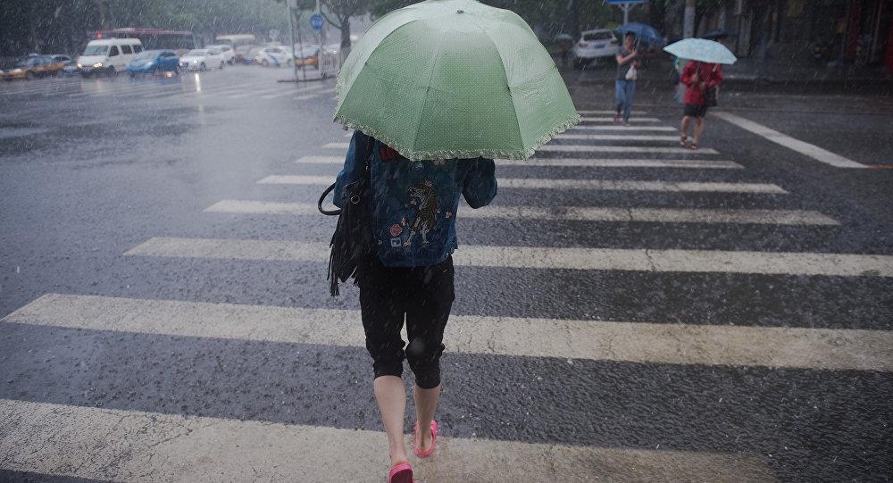 Девушка с зонтом переходит улицу. Архивное фото