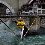 Швейцариянын Берна шаарындагы Ааре дарыясын керилген жип аркылуу кесип өткөн киши