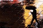 Мужчина с зонтом идет по улице во время дождя. Архивное фото