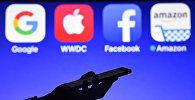 Мужчина со смартфоном в руке на фоне логотипов Google, Apple, Facebook и Amazon. Архивное фото