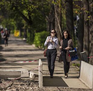 Девушки переходят по мосту на ремонтируемой улице в Бишкеке. Архивное фото