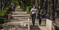 Девушки переходят по мосту на ремонтируемой улице в Бишкеке