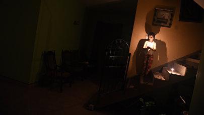 Молодая девушка держит свечу после отключения электроэнергии в своем доме. Архивное фото