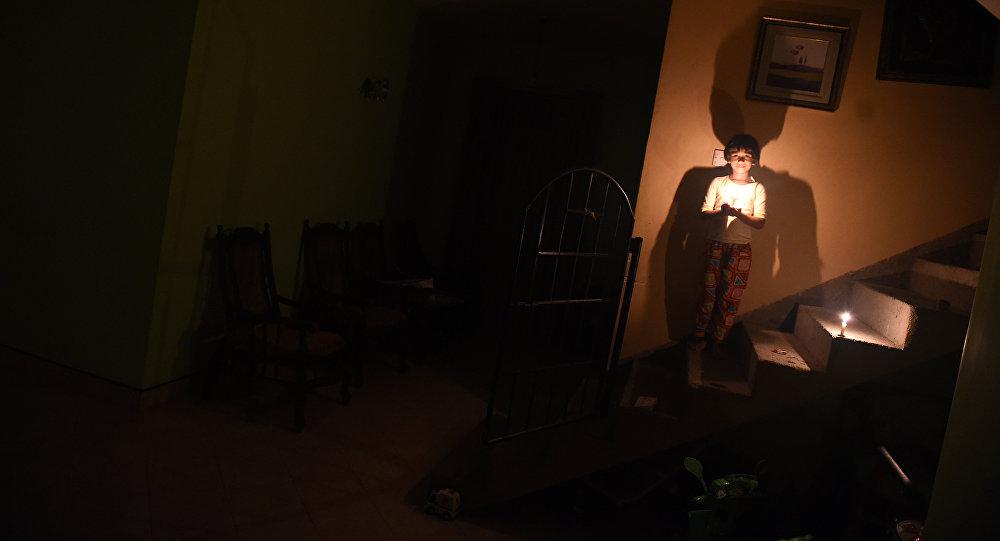 Девочка держит свечу во время отключения электроэнергии. Архивное фото