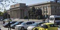 Автомобили припаркованные рядом с зданием Правительства Кыргызской Республики на старой площади Бишкеке.