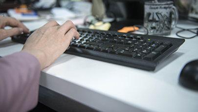Женщина за столом печатает на компьютере. Архивное фото