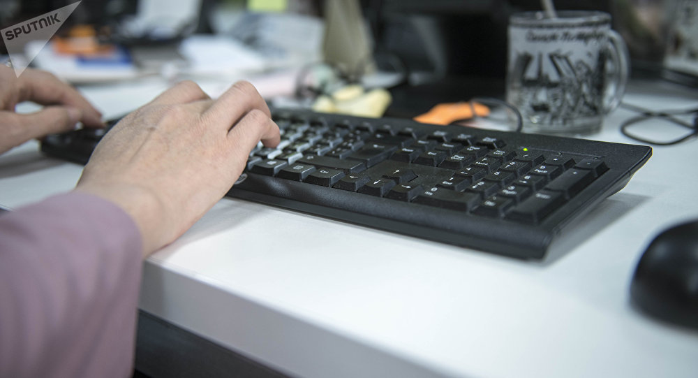 Клавиатурада жазып аткан киши. Архивдик сүрөт