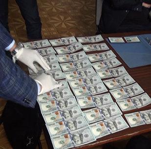 Папкага катылган доллар. ЖАМК кызматкеринин пара берүү учуру