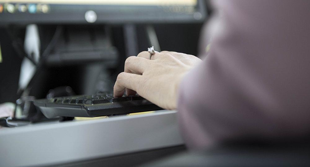 Женщина печатает на клавиатуре во время работы на компьютере. Архивное фото