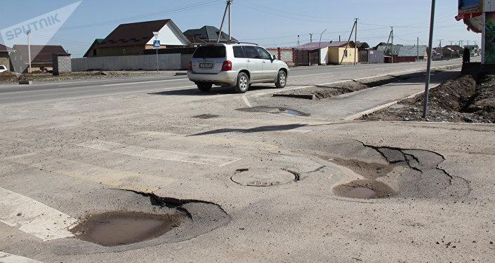 Разрушенное дорожное покрытие на одной из улиц Бишкека. Архивное фото