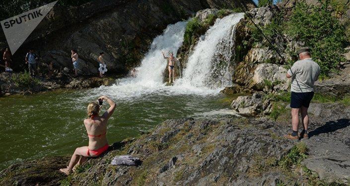Отдыхающие купаются у водопада в горах. Архивное фото