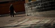 Пожилая женщина идет по улице. Архивное фото