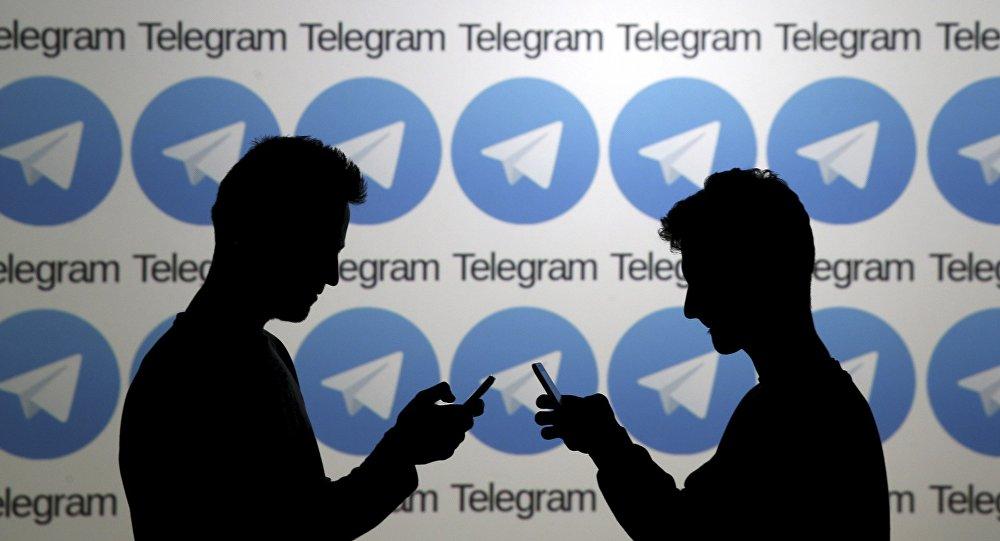 Двое мужчин позируют со смартфонами перед экраном, на котором показаны логотипы Telegram. Архивное фото