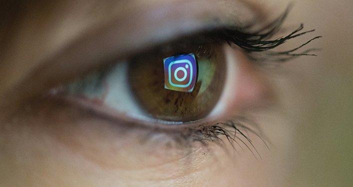 Логотип Instagram отсвечивается от глаз человека.