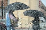 Женщины с зонтом идут по улице во время дождя. Архивное фото