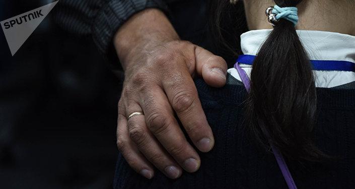 Мужчина держит девочку за плечо. Иллюстративное фото