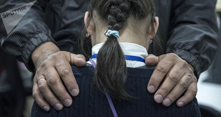 Мужчина кладет руки на плечи девочки. Иллюстративное фото