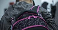 Мужчина с школьным рюкзаком на спине. Иллюстративное фото