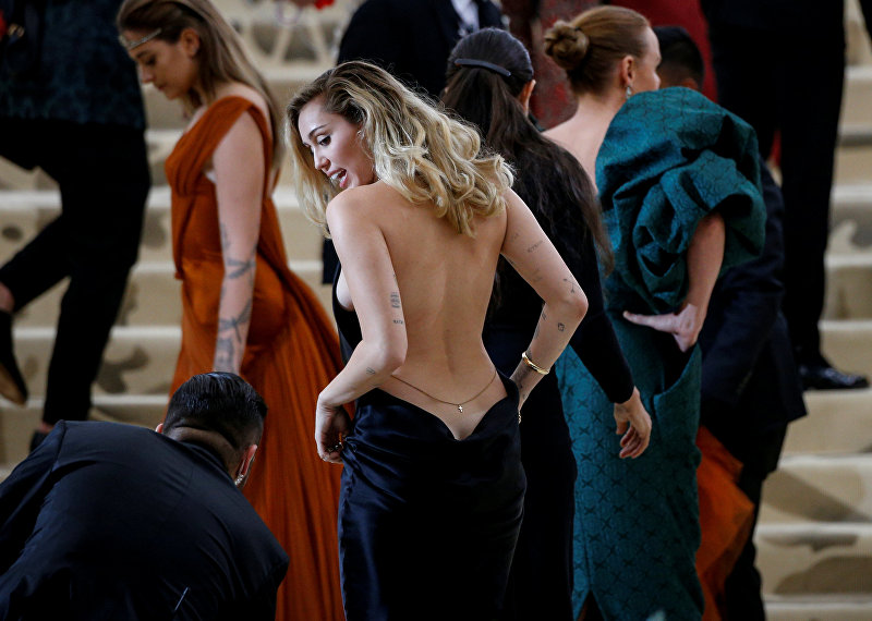 Певица Майли Сайрус стала гостьей Met Gala в пикантном черном платье, которое полностью оголило ее спину
