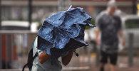 Человек c зонтом во время сильного ветра и дождя. Архивное фото