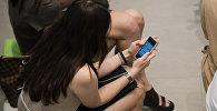 Девушка со смартфоном в руке. Архивное фото