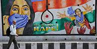 Человек проходит мимо граффити, изображающего сообщение в знак протеста против изнасилования в Джамму. Архивное фото