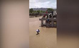 Мужчина с ребенком переходит вброд реку Нарын из-за недостроенного моста. Видео