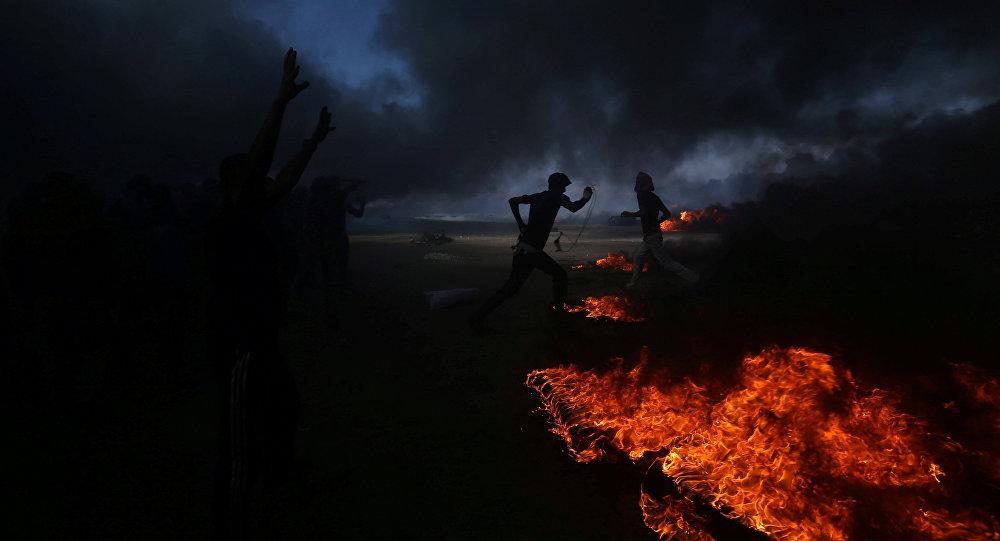 Палестинские демонстранты бегут во время акции протеста на границе между Израилем и Газой в южной части сектора Газа. Архивное фото