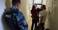 Охранник предприятия Сириус и журналисты у офиса РИА Новости Украина в Киеве, где СБУ проводит обыски. Архивное фото