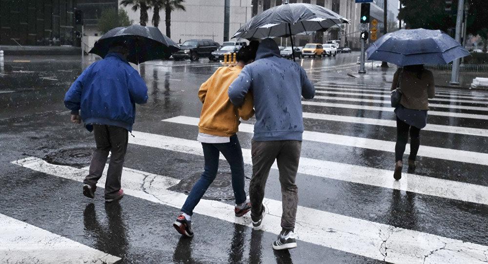 Люди с зонтами переходят улицу во время дождя. Архивное фото