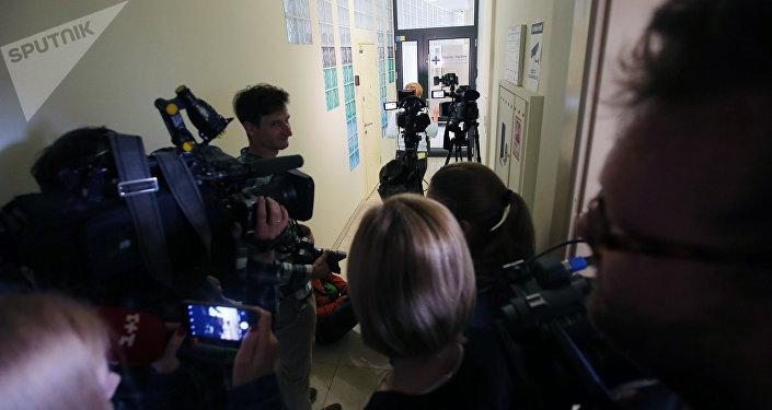 Журналисты у офиса РИА Новости Украина в Киеве, где СБУ проводит обыски.