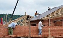 Рабочие во время строительства дома. Архивное фото