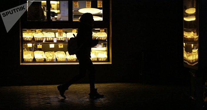 Прохожий возле кофейни ночью. Архивное фото