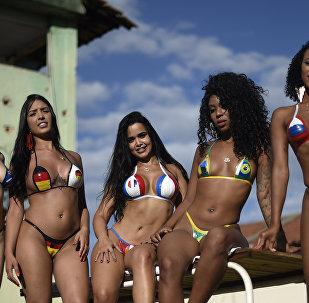 Девушки в купальниках из изоленты в виде флагов некоторых стран-участников чемпионата мира по футболу (Бразилия)