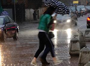 Девушки с зонтом во время сильного дождя. Архивное фото