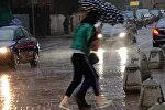 Пешеходы на улице во время сильного дождя. Архивное фото