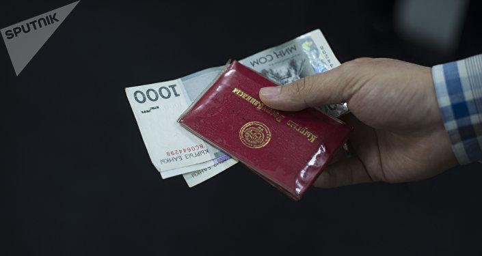 Мужчина дает удостоверение сотрудника МВД КР с деньгами