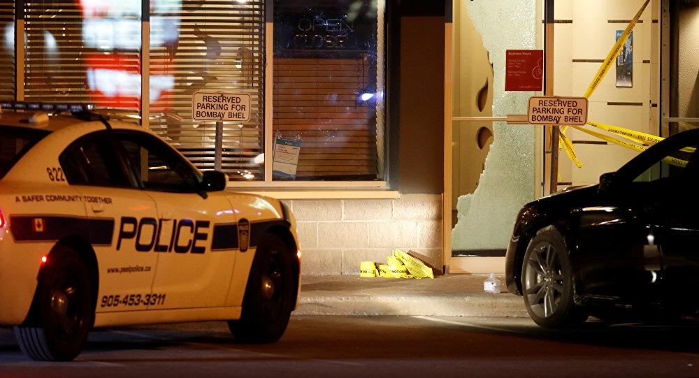 Полицейская машина припаркована перед разбитым стеклом в ресторане Bombay Bhel, где два неизвестных мужчины оставили бомбу поздно в Миссиссауге, Онтарио. Канада, 25 мая 2018 года