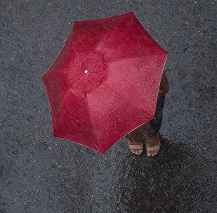 Женщина с зонтом во время сильного дождя. Архивное фото