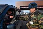 Пограничник во время проверки документов у граждан на контрольно-пропускном пункте Чалдыбар-Автодорожный в Чуйской области на кыргызско-казахской границе. Архивное фото