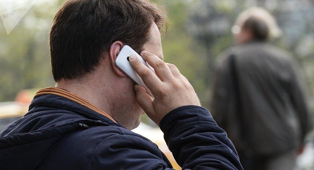 Телефононд сүйлөшүп аткан киши. Архивдик сүрөт