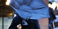 Человек держит зонтик во время сильного ветра. Архивное фото