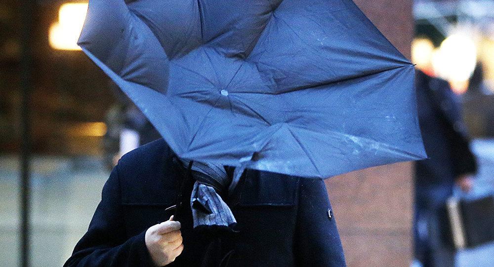 Человек держит повернутый зонтик во время сильных ветров. Архивное фото