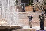 Туристы с камерой у фонтана на площади Ала-Тоо в Бишкеке. Архивное фото