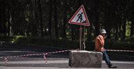 Рабочий на одной из улиц Бишкека закрытом на ремонт. Архивное фото