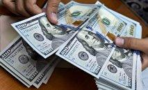 Мужчина пересчитывает доллары США. Архивное фото