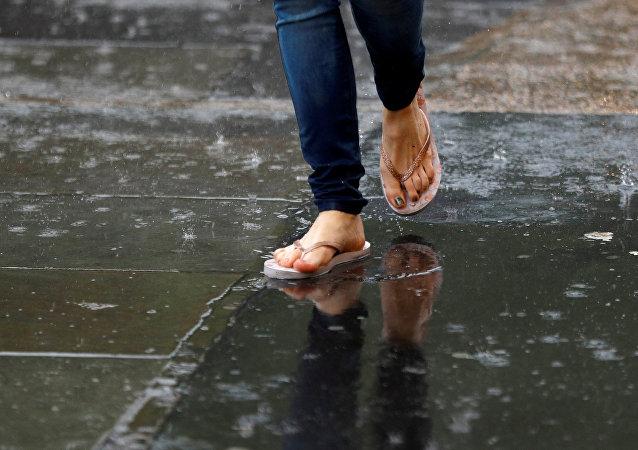 Женщина в шлепанцах во время дождя. Архивное фото