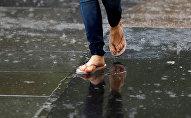 Женщина в шлепанцах во время сильного дождя. Архивное фото