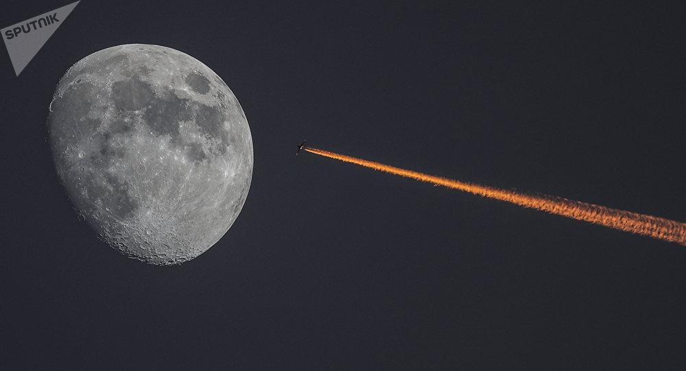 Самолет в небе над Москвой на фоне растущей луны. Архивное фото